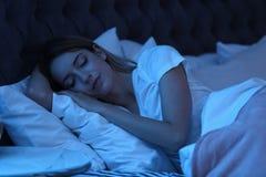 Ung kvinna som sover i säng på natten arkivfoton