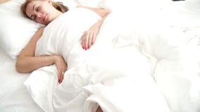 Ung kvinna som sover i säng på sovrumsikt från över drömma kvinna för underlag lager videofilmer