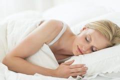 Ung kvinna som sover i säng Royaltyfri Bild
