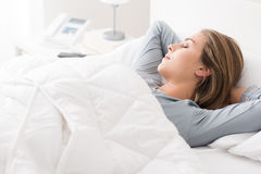 Ung kvinna som sover i sovrummet royaltyfri bild