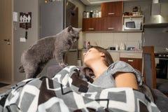 Ung kvinna som sover med hennes katt arkivfoto