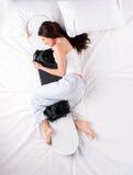 Ung kvinna som sover och kramar snowboarden Royaltyfri Fotografi