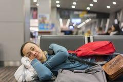 Ung kvinna som sover på flygplatsen, medan vänta på hennes flyg Trött kvinnlig handelsresande som sover på airpotavvikelseportarn royaltyfri bild
