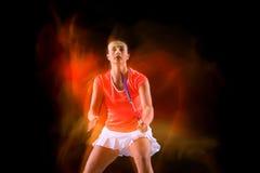 Ung kvinna som spelar badminton över svart bakgrund Royaltyfri Foto