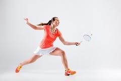 Ung kvinna som spelar badminton över vit bakgrund Arkivbilder