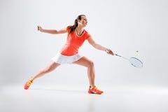 Ung kvinna som spelar badminton över vit bakgrund Royaltyfri Bild