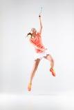 Ung kvinna som spelar badminton över vit bakgrund Arkivfoto
