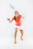Ung kvinna som spelar badminton över vit bakgrund Royaltyfria Bilder