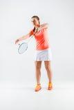 Ung kvinna som spelar badminton över vit bakgrund Arkivfoton