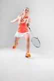 Ung kvinna som spelar badminton över vit bakgrund Arkivbild