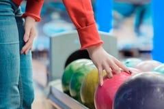 Ung kvinna som spelar bowling på sportklubban close upp royaltyfri foto