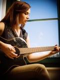 Ung kvinna som spelar den akustiska gitarren Arkivfoto