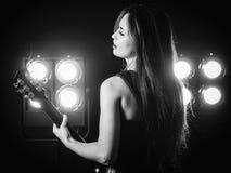 Ung kvinna som spelar den elektriska gitarren på etapp Arkivfoton