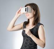 Ung kvinna som spelar exponeringsglas för en virtuell verklighet Fotografering för Bildbyråer