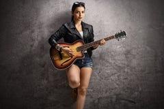 Ung kvinna som spelar gitarren och benägenhet på en rostig grå vägg fotografering för bildbyråer