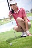 Ung kvinna som spelar golf Arkivbild