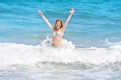 Ung kvinna som spelar i stora vågor i havet Arkivbild