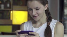 Ung kvinna som spelar leken på smartphonen stock video