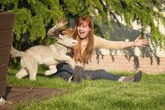 Ung kvinna som spelar med hundkapplöpningen Royaltyfri Fotografi