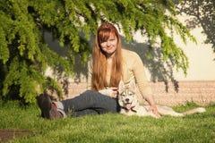 Ung kvinna som spelar med hundkapplöpningen Royaltyfri Foto