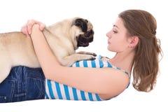 Ung kvinna som spelar med mopshunden som isoleras på vit Arkivfoton