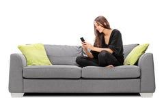 Ung kvinna som spelar på hennes mobiltelefon Fotografering för Bildbyråer