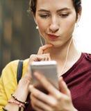 Ung kvinna som spelar på hennes telefon arkivbilder