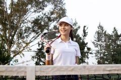 Ung kvinna som spelar tennis p? domstolen arkivfoto