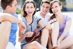 Ung kvinna som spelar ukulelet för vänner Arkivbild