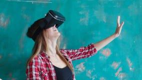 Ung kvinna som spelar videospelet med pappvirtuell verklighethörlurar med mikrofon arkivfilmer