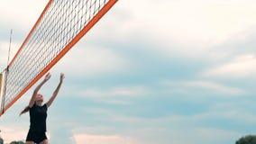 Ung kvinna som spelar volleyboll på stranden i ett lag som ut bär en attack som slår bollen Flicka i ultrarapidslag lager videofilmer