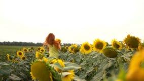 Ung kvinna som stöter ihop med fältet från solrosor, ultrarapid lager videofilmer