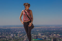 Ung kvinna som staing på kullen med stadssikt, Almaty, Kazakhsta Arkivfoton