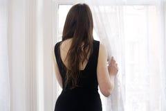 Ung kvinna som stirrar ut ur fönster Arkivfoton
