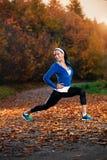 Ung kvinna som sträcker, innan att köra i den tidiga aftonen i th Fotografering för Bildbyråer