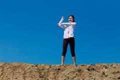 Ung kvinna som sträcker på bergslinga Arkivfoto