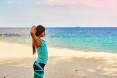Ung kvinna som sträcker på stranden Fotografering för Bildbyråer