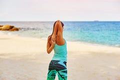 Ung kvinna som sträcker på stranden Royaltyfria Foton
