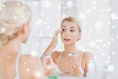 Ung kvinna som sätter på kontaktlinser på badrummet Royaltyfri Fotografi