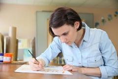 Ung kvinna som studerar dekorativ målning Royaltyfri Fotografi