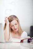 Ung kvinna som studerar från en lärobok Royaltyfria Bilder