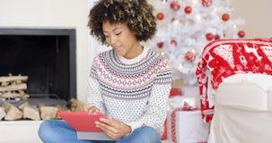 Ung kvinna som surfar internet på jul Arkivbilder
