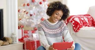 Ung kvinna som surfar internet på jul Arkivfoto