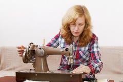 Ung kvinna som syr tyg genom att använda en symaskin Fotografering för Bildbyråer