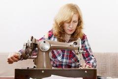 Ung kvinna som syr tyg genom att använda en symaskin Arkivbild