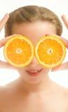 Ung kvinna som täcker henne ögon med orange skivor Royaltyfria Foton