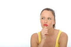 Ung kvinna som tänker eller grubblar över ett problem Arkivbild