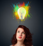 Ung kvinna som tänker med lightbulben ovanför hennes huvud Royaltyfri Bild
