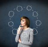 Ung kvinna som tänker med molncirkulation runt om hennes huvud Arkivbilder