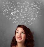 Ung kvinna som tänker med sociala nätverkssymboler ovanför hennes huvud Royaltyfria Foton